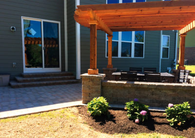 Paver patio with stone wall and pergola - AFTER