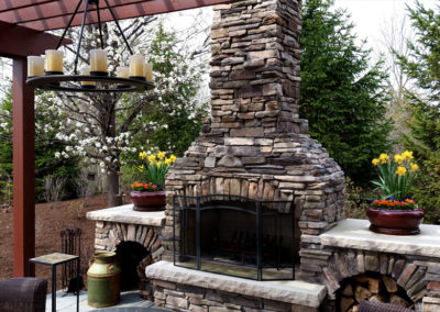 Outdoor living space with fireplace, pergola, and lighting.