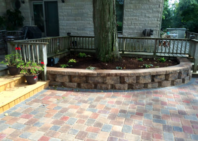 Paver patio with raised stone wall flower bed.
