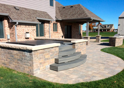 Paver patio with hot tub enclosure and built-in grill.