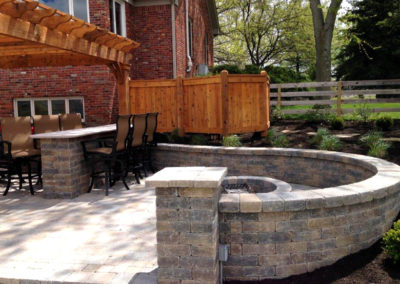 Paver patio with pergola, bar, fire pit and sitting wall.