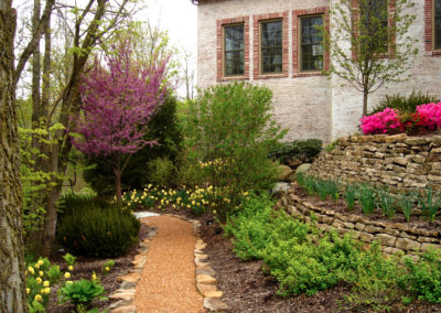 Stone walkway lined with seasonal flowers.