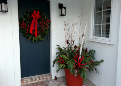 Front porch with winder container and fresh green wreath.